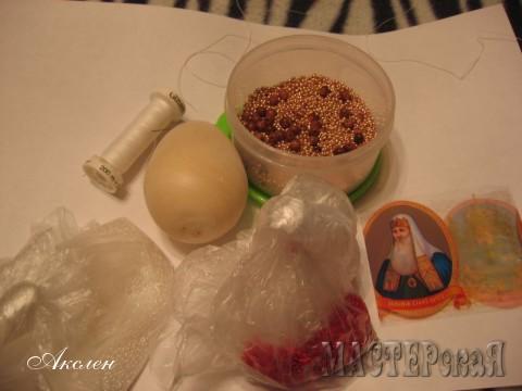 Нам понадобится деревянная болванка яичка, бисер трех цветов, термо наклейка,лавсановые нитки, в горячей воде закрепляем наклейку, если яичко большое то наклейка разрезается и крепится скотчем, потом вырезать картинку и по центру с двух сторон опять таки прикрепить скотчем на сухое яичко